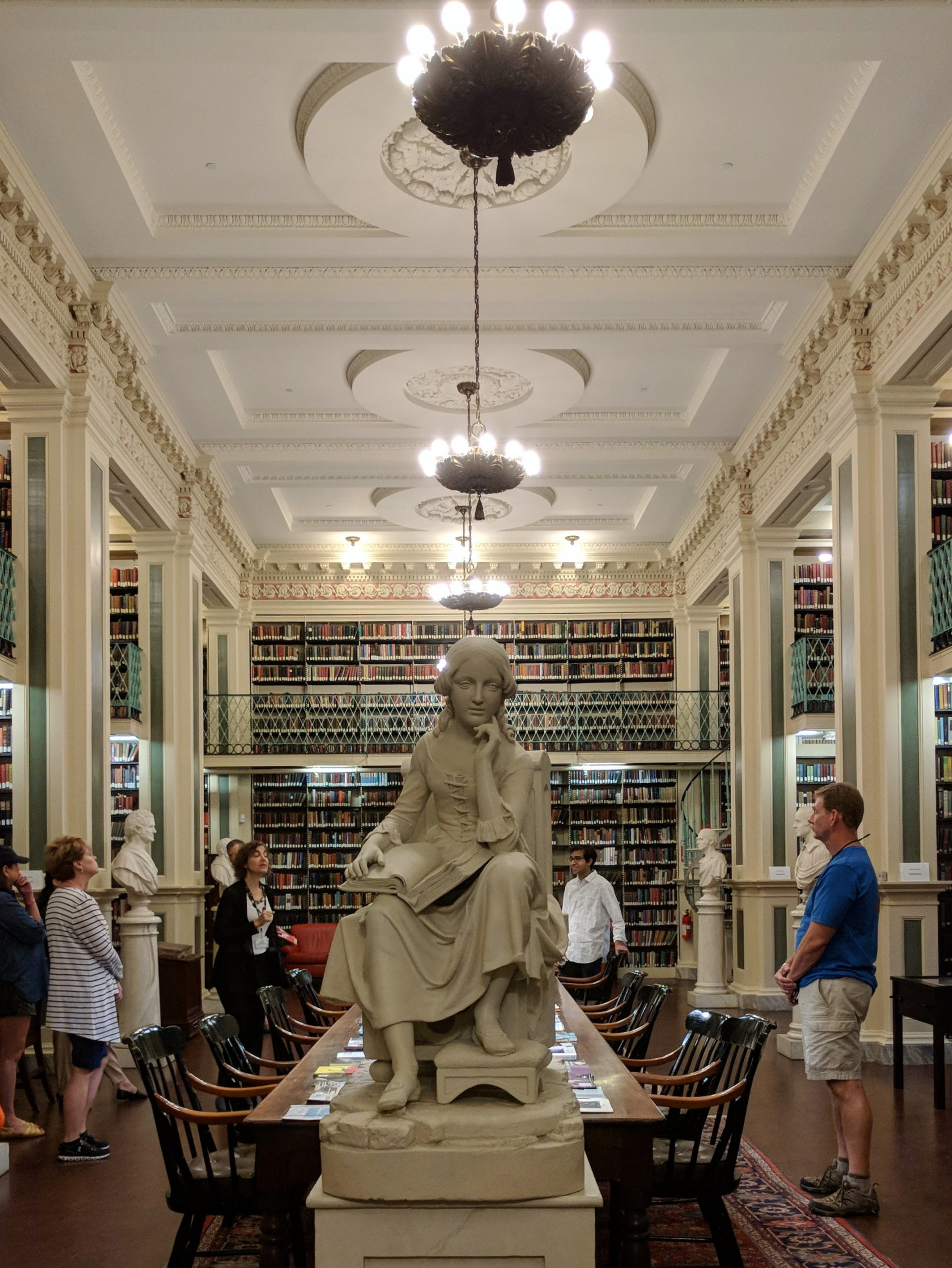 Reading room with a statue of a thinking woman and rows of books and chandeliers in the background