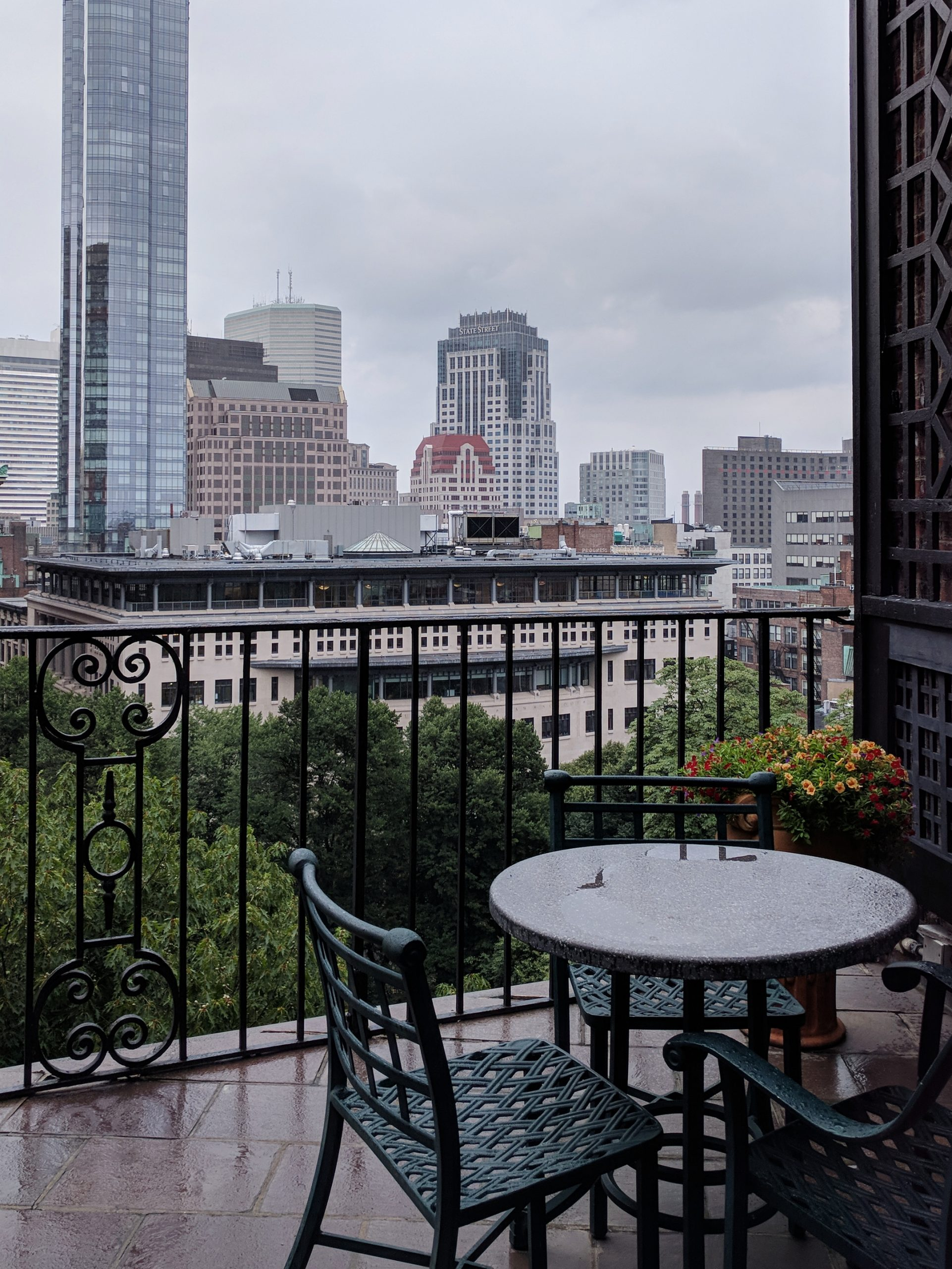 The Boston skyline from the fifth floor patio of the Boston Athenaeum on a gray day with a patio table in the foregroud