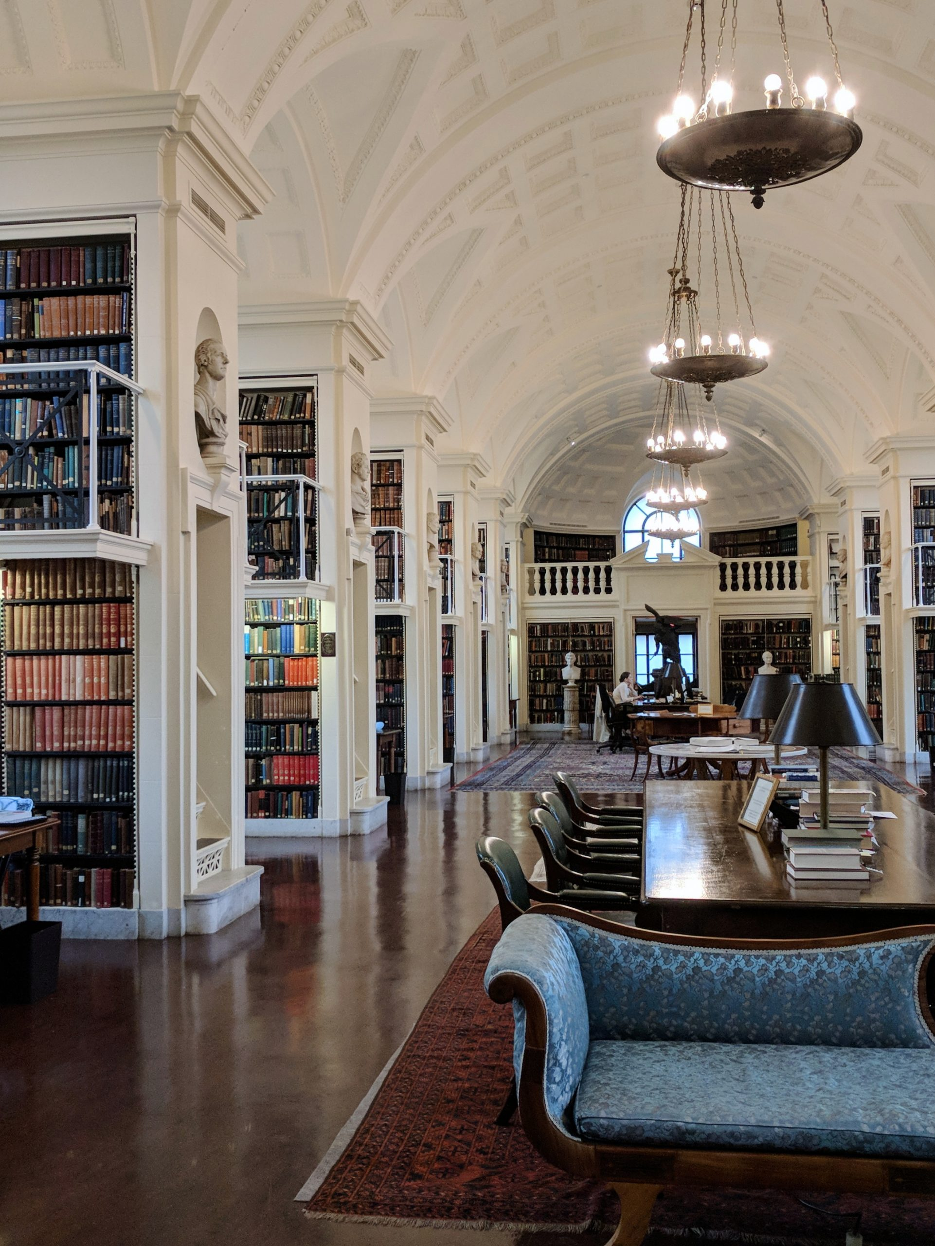 The very instagrammable fifth floor reading room of the Boston Athenaeum, with tall, white arched ceilings and rows of colorful books