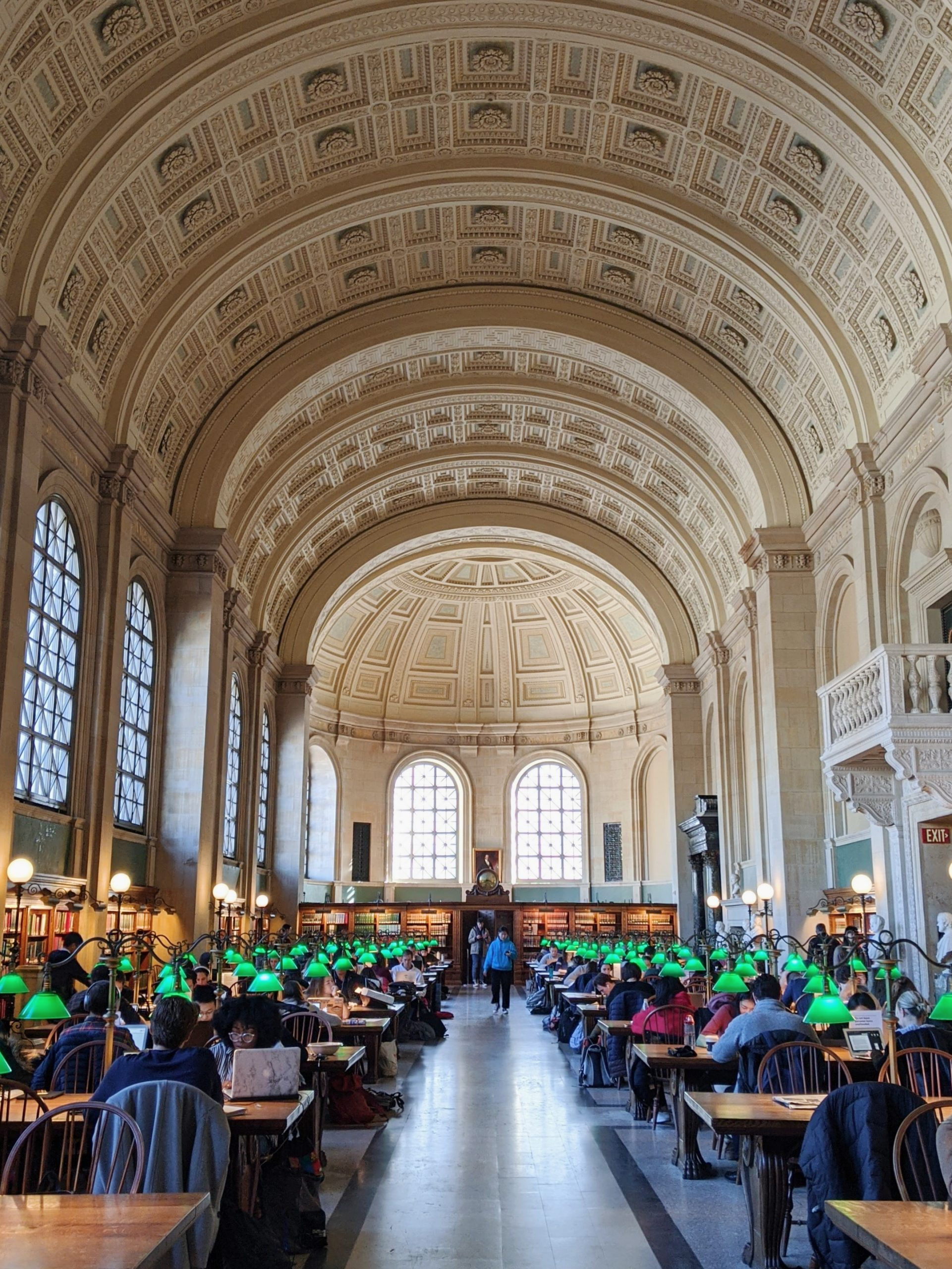 Boston public library main reading room - features high arched ceilings and many desks with the iconic green lamps