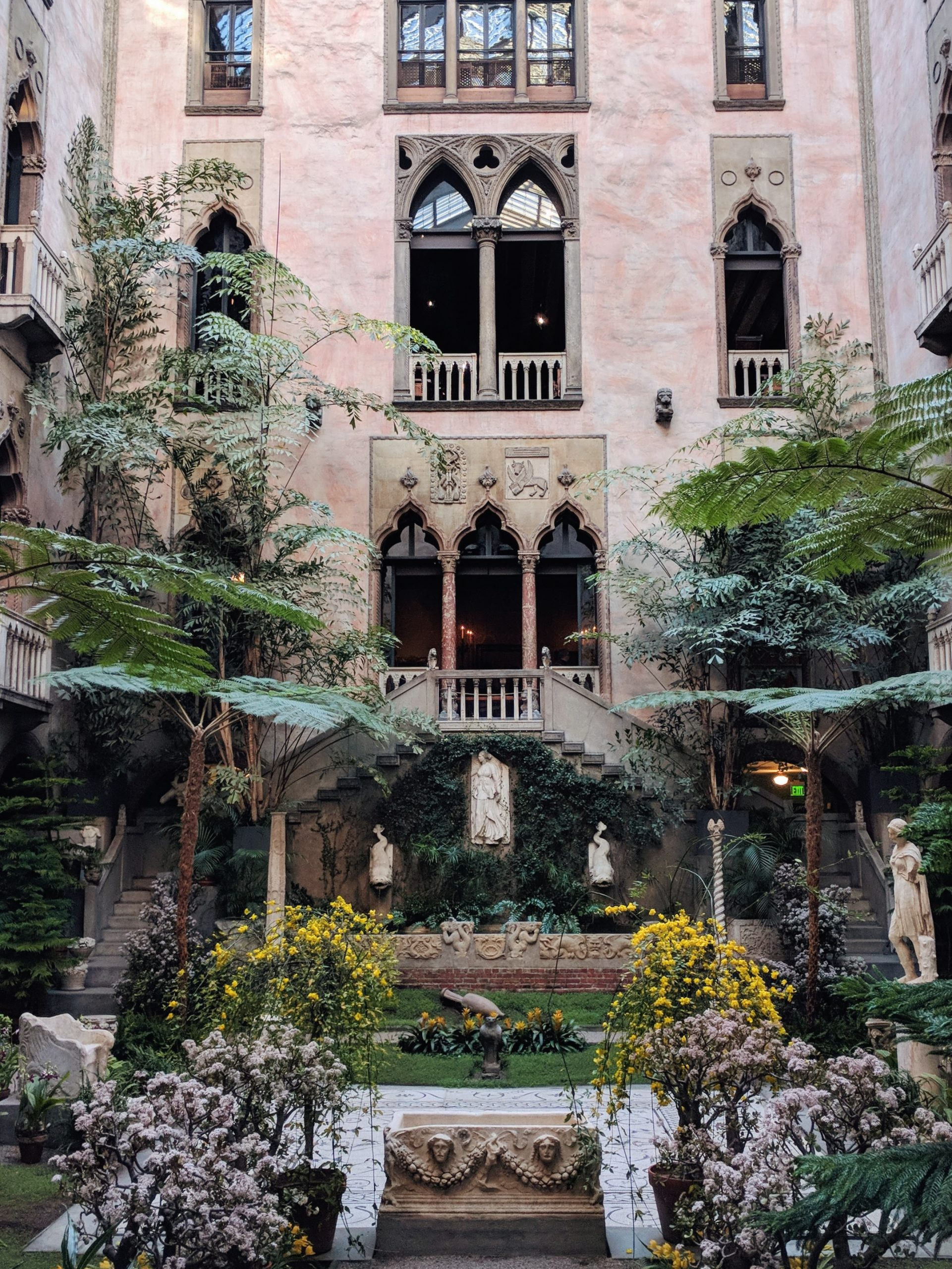 Isabella Stewart Gardner museum courtyard with lush green trees and plants