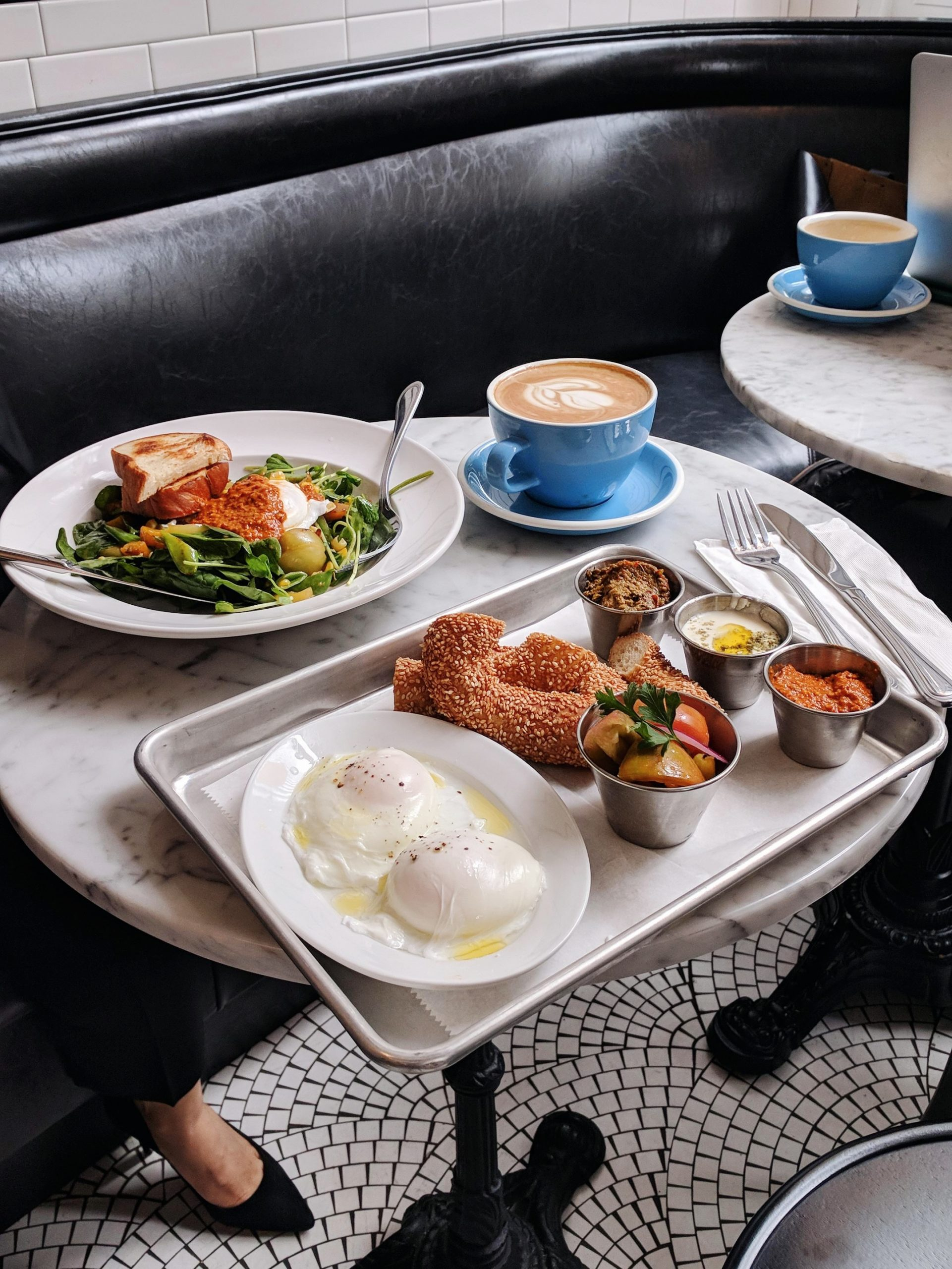 Flatlay of a tray of food, a coffee, and a plate of salad on a white marble table