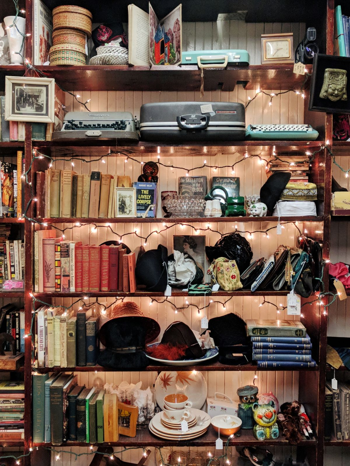 Finders Keepers antique store in Lee, MA that's decorated with string lights and full of books, china, typewriters, and hats