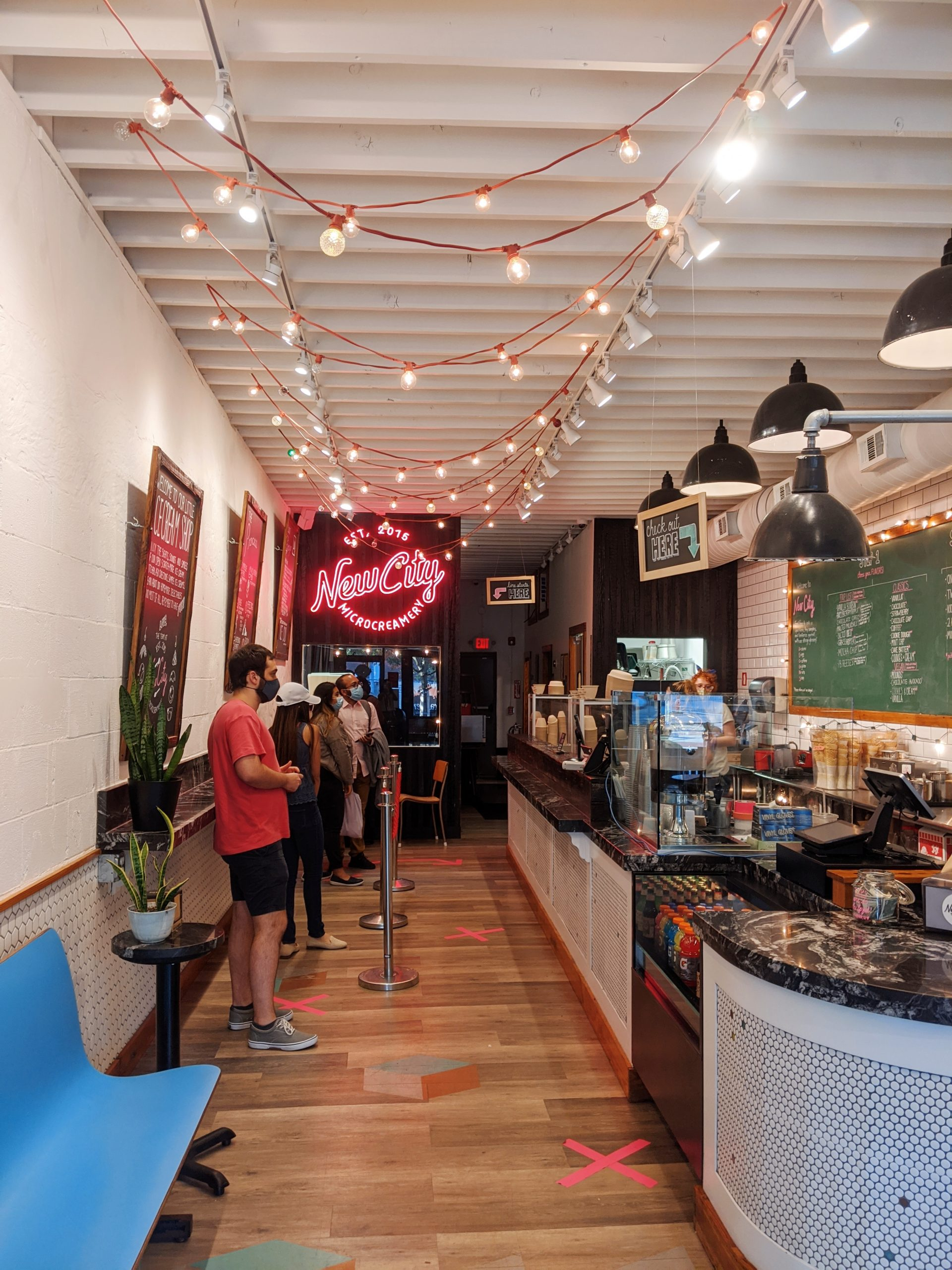 aesthetic ice cream shops etting with hanging lights and a pink neon sign that says 'New City Microcreamery'