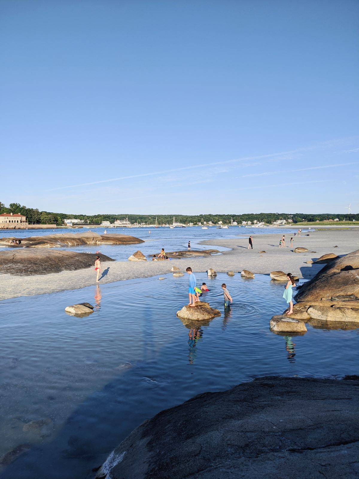 The exposed rocks of Wingaersheek Beach at low tide, with kids and adults wading in the water