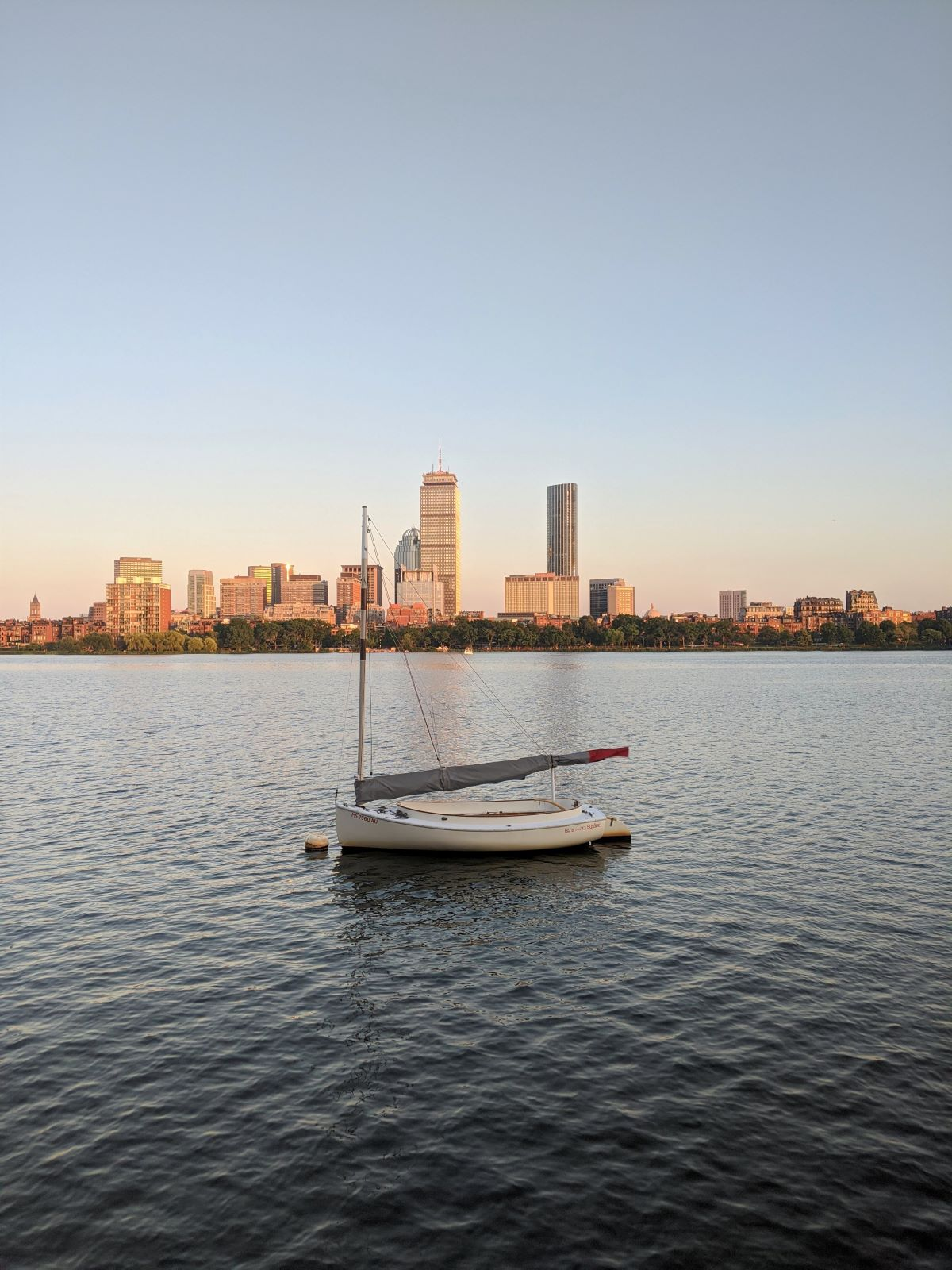 a sailboat on the Charles RIver with the Boston skyline in the background at sunset