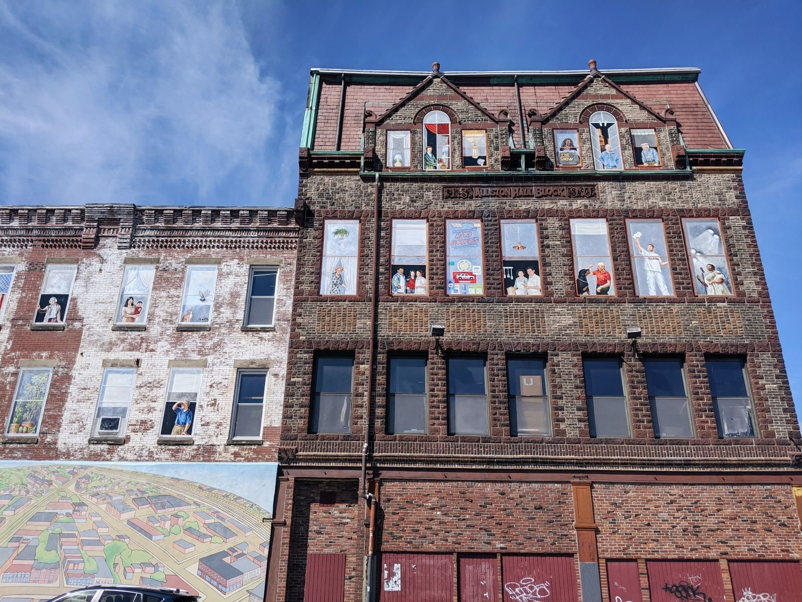 murals painted into the windows of a brick building in Allston