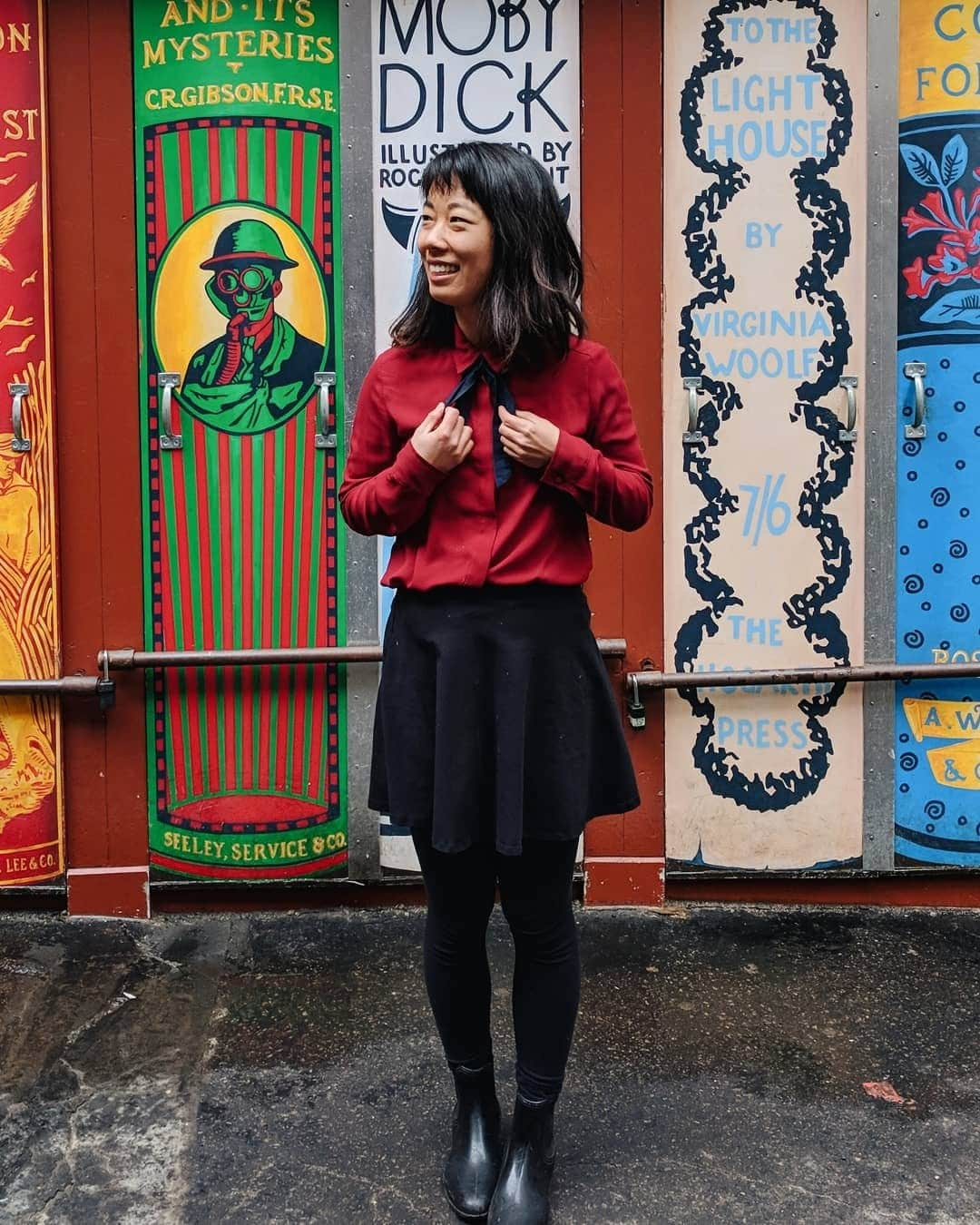 me standing in front of a colorful mural of book spines at Brattle Book Shop