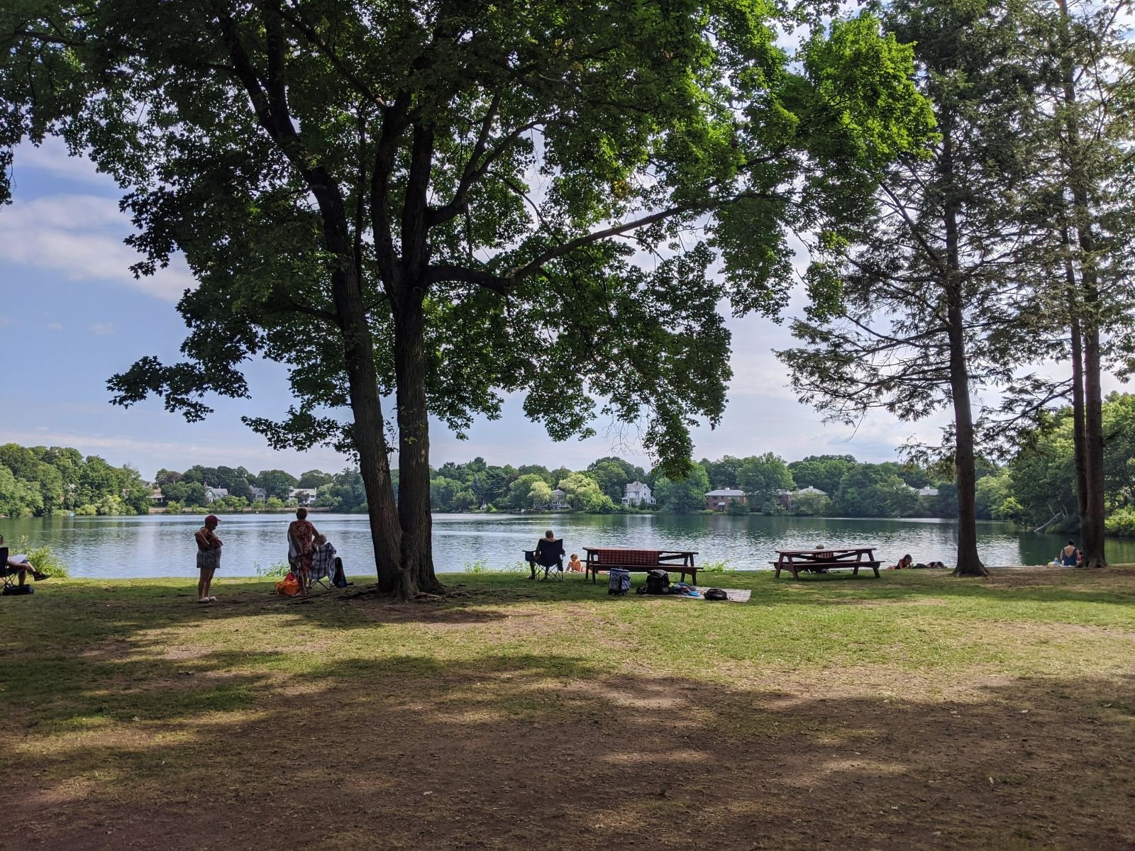 grassy picnic area shaded by trees with Crystal Lake in the background