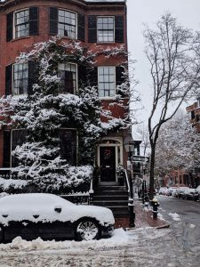 Ivy-covered brick house in the snow at Louisburg Square
