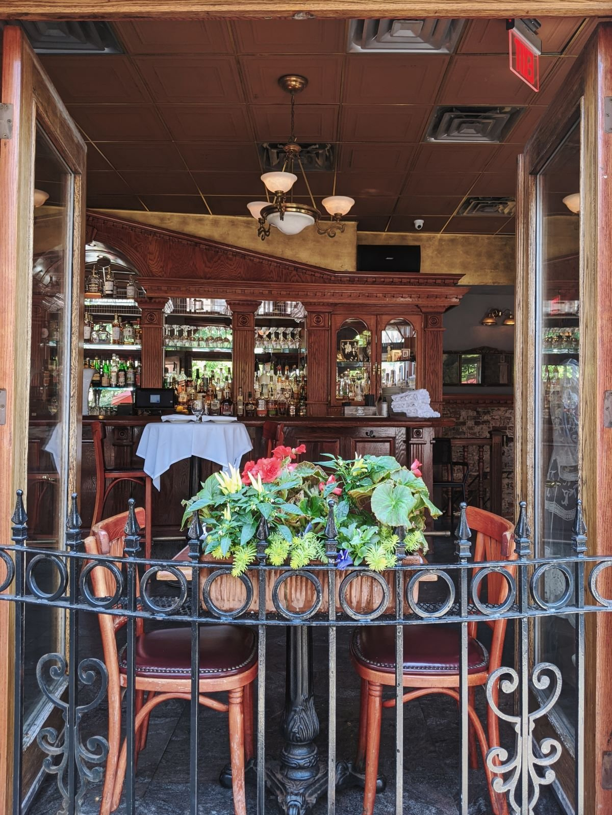 looking into a North End restaurant through the open window with a table for two in the opening