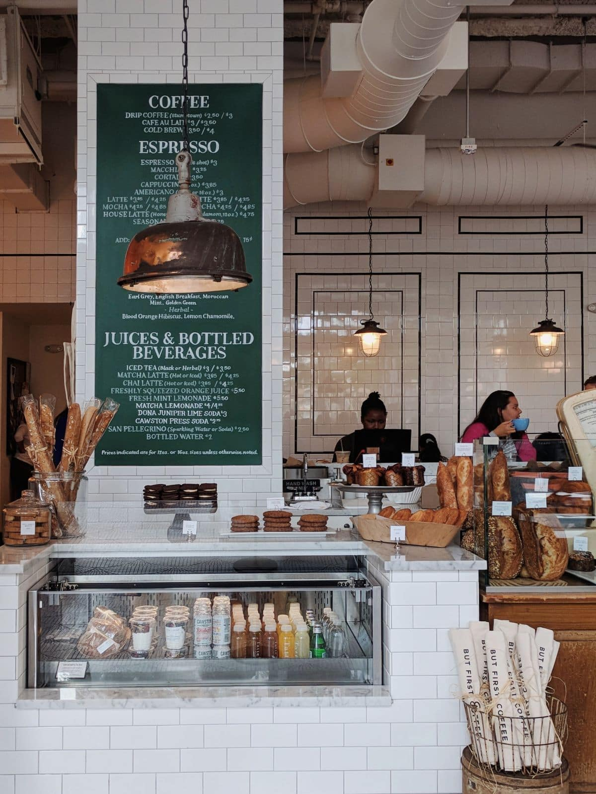 Tatte Bakery counter with baguettes, pastries, and hanging lamps