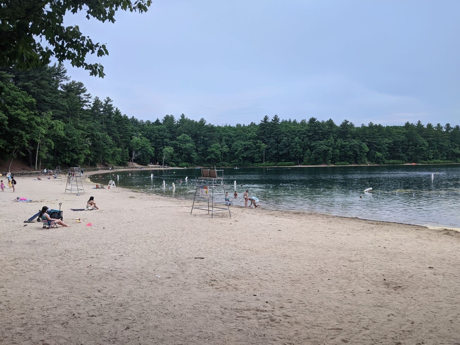 Walden Pond on a cloudy day, with only a handful of people on the beach