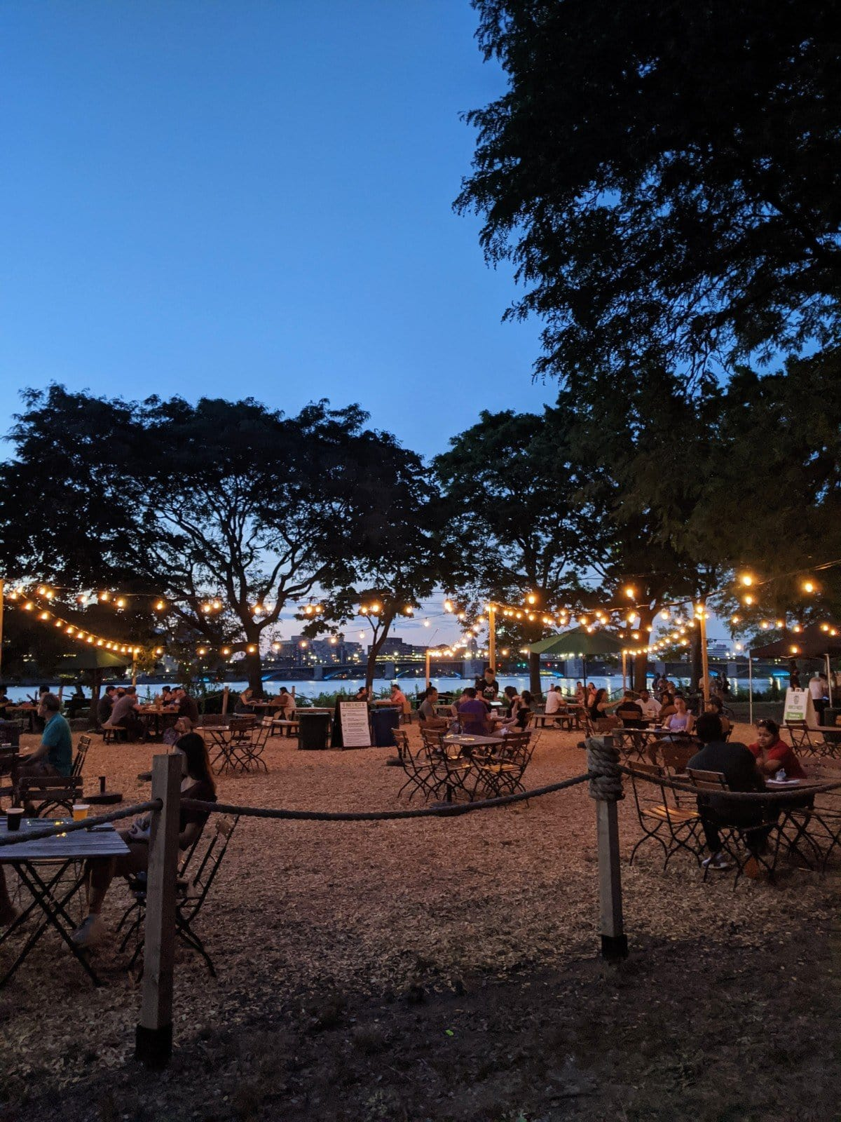 Beer garden on the Charles Esplanade at sunset with distant tables and hanging lights, photo by Roaming Boston