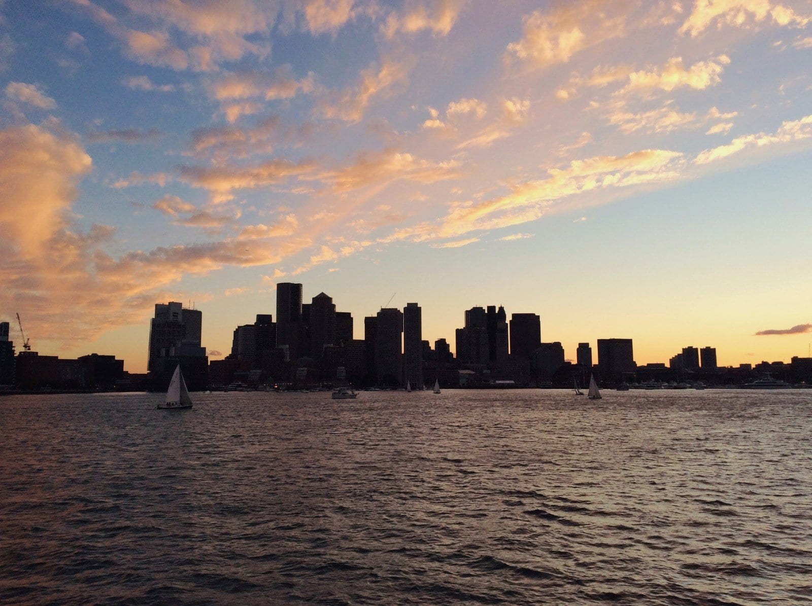 silhouette of the Boston skyline at sunset, photo by Roaming Boston