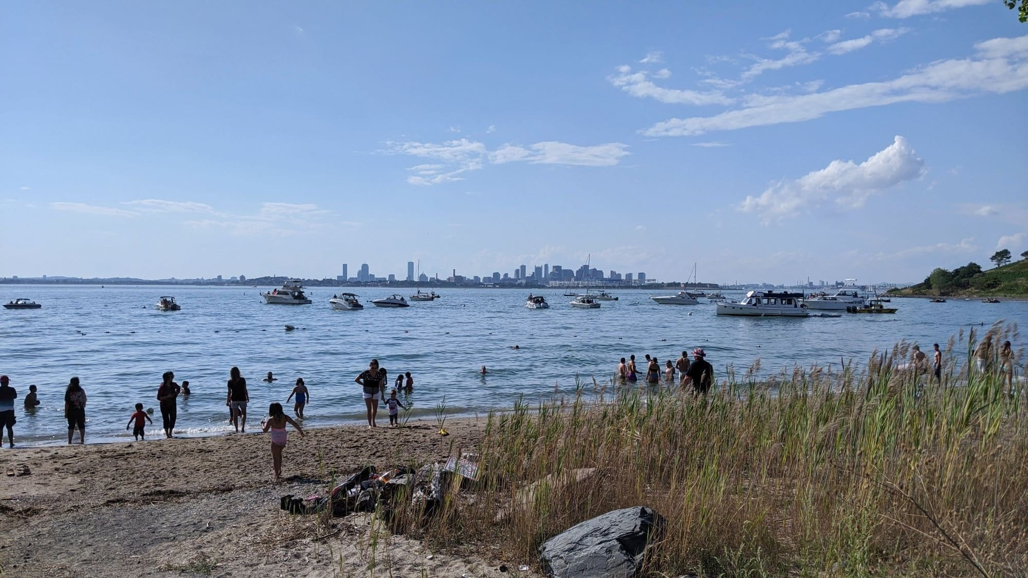 Spectacle Island beach with boats and the Boston skyline in the distance